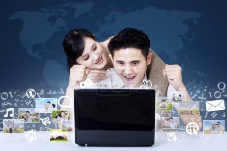 Excited couple looking at digital photos on blue world map