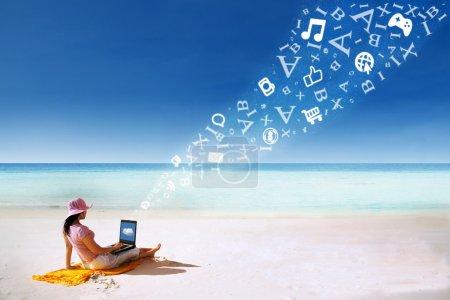 Asian woman using laptop at beach
