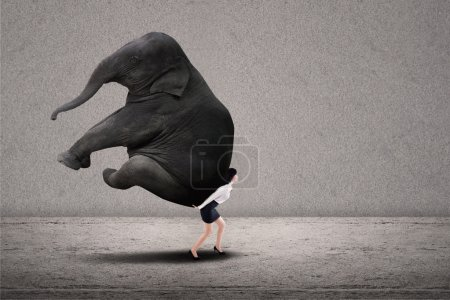 Businesswoman lifting heavy elephant