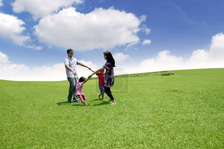 Happy asian family playing on the field. They are ...