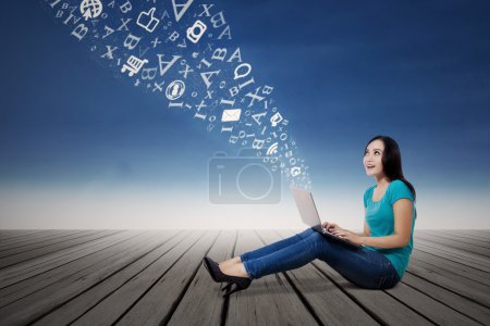 Female student looking at words with laptop outdoor
