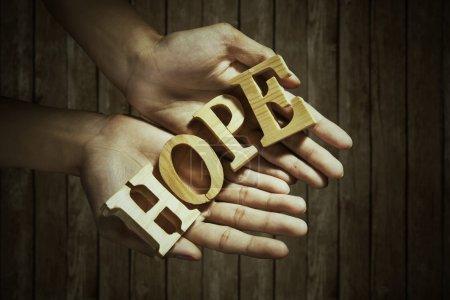 Photo pour Gros plan des mains masculines tenant un mot d'espoir - image libre de droit