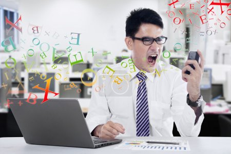 Young businessman screaming at mobilephone