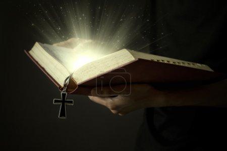 Photo pour Mains d'homme tenant la bible sainte et le chapelet en bois avec des rayons magiques - image libre de droit