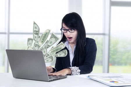 Shocked businesswoman looking money at laptop
