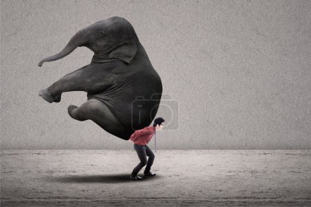 Photo for Businessman is lifting big elephant on grey background - Royalty Free Image