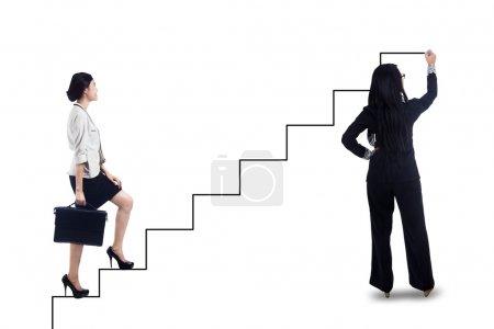 Photo pour Femme d'affaires intensification dans les escaliers pour obtenir son succès avec la femme d'affaires de dessin de l'escalier - image libre de droit