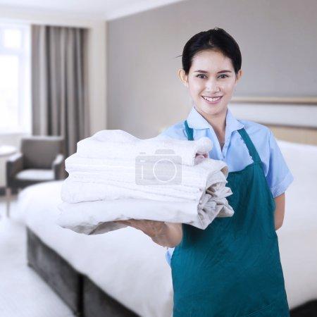 Photo pour Jeune femme de ménage souriante tenant des serviettes dans la chambre d'hôtel - image libre de droit
