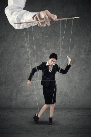 Photo pour Femme d'affaires suspendue à une ficelle et contrôlée par une main - image libre de droit