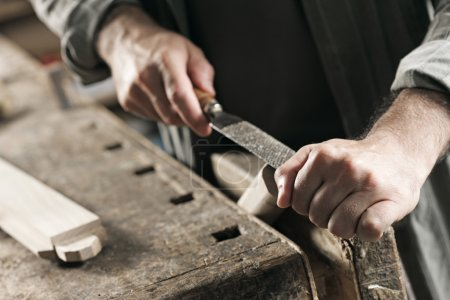 Photo for Carpenter working on a piece of wood with a file - Royalty Free Image