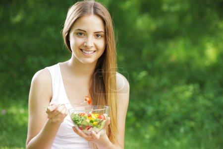 Foto de Retrato de feliz hermosa mujer joven comiendo ensalada de verduras - Imagen libre de derechos