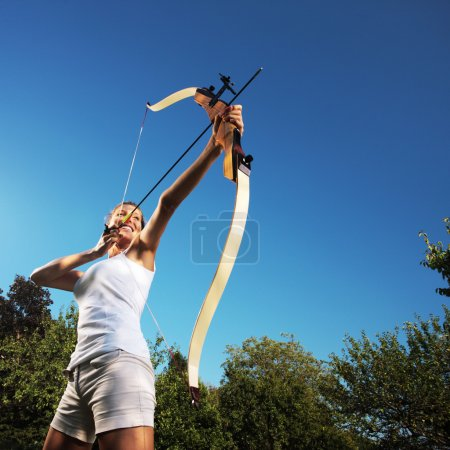 Photo pour Belle femme pliant un arc et visant dans le ciel - image libre de droit