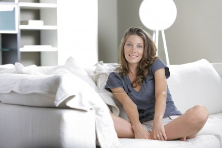 Photo for Relaxing at home. Portrait of a young woman smiling on white couch - Royalty Free Image