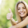 Young smiling blond female outdoors showing thumb ...