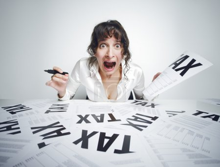 Photo for Young frightened woman shouting out while sitting at her paperwork-covered desk with a marker in one hand and a tax bill in the other one - Royalty Free Image