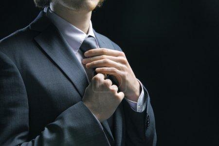 Business man adjusting tie