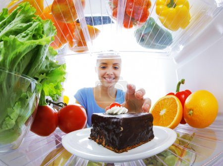 Photo for Young woman stops her diet and look for a cake in the refrigerator - Royalty Free Image