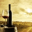 Red wine bottle and wine glass on wodden barrel...
