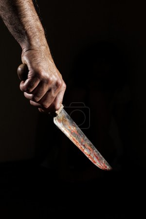 Photo for Man with bloody knife, hand close up, dark background - Royalty Free Image