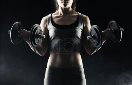 Photo for Young woman lifting the dumbbells - Royalty Free Image