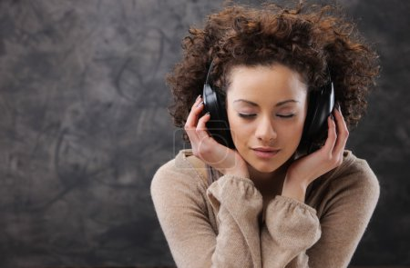 Photo for Young beautiful woman listening to music with headphones - Royalty Free Image