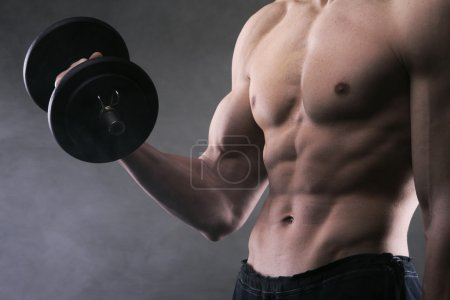 Photo for Muscular male athlete is training by lifting dumbbells - Royalty Free Image