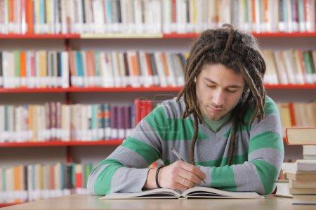 Photo pour Jeune étudiant masculin à la bibliothèque, étudiant - image libre de droit