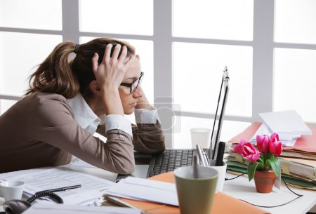 Photo for Young and beautiful businesswoman tired from work in the office.Woman holding her head - Royalty Free Image