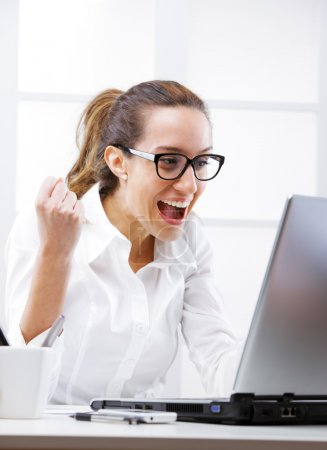 Young businesswoman cheering, screaming at laptop...