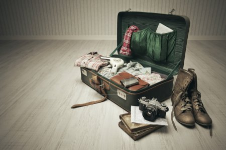 Photo for Vintage suitcase open on a wood floor in an empty room - Royalty Free Image