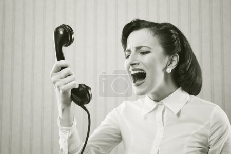 Photo for Young Woman shouting into telephone - Royalty Free Image