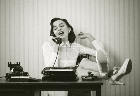 Photo for Business woman puts her feet up on her desk on the phone - Royalty Free Image
