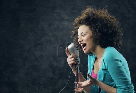 Photo pour Jeune chanteuse aux cheveux bouclés bruns chantant une chanson - image libre de droit