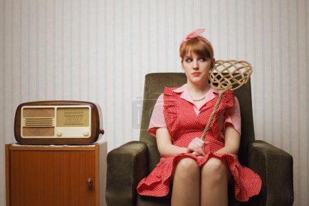 Photo pour Portrait ironique d'une femme au foyer rétro assise dans un fauteuil - image libre de droit