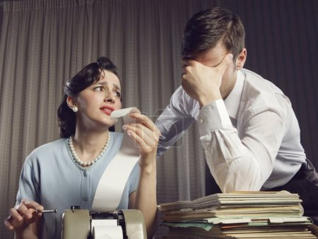 Photo for Stressed man and woman looking at their bills in the living-room at home - Royalty Free Image