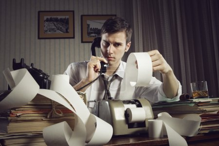 An male accountant at telephone preparing income t...