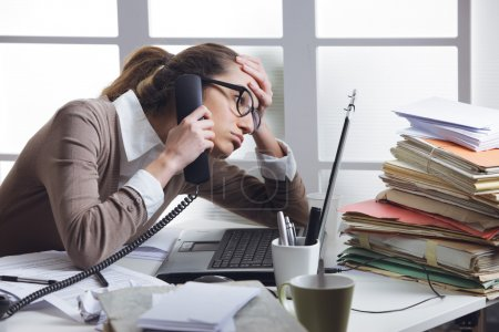 Photo for A stressed business woman looks tired she answer telephones in her office - Royalty Free Image