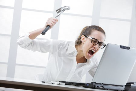 Freaked out businesswoman with a hammer ready to s...