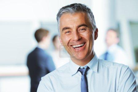 Photo pour Mature homme d'affaires avec des collègues en arrière-plan - image libre de droit