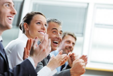 Photo for Group of cheerful businesspeople sitting in a row on a presentation and clapping - Royalty Free Image