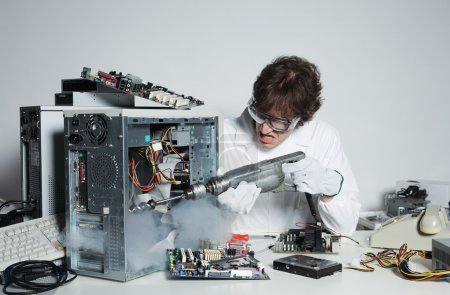 Photo for Crazy computer technician is trying to repair a computer with a drill - Royalty Free Image