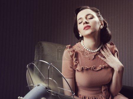 Foto de Hermosa mujer usando un ventilador para enfriar - Imagen libre de derechos