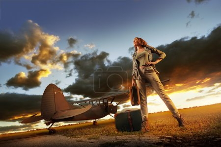 Photo for Fashion young womanl with a suitcase. Airplane in the background. - Royalty Free Image