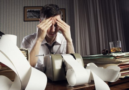 Photo for Tired businessman is sitting at a table full of paperwork - Royalty Free Image