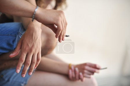 Photo for Cropped shot of two teenagers smoking cigarettes - Royalty Free Image