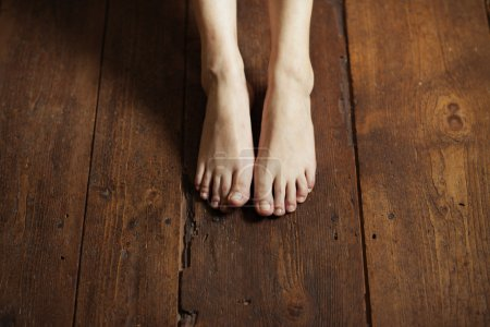 Photo for Cropped image of female bare feet on a wooden floor - Royalty Free Image