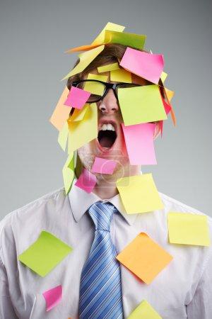 Photo pour Employé de bureau avec des post-its sur son visage - image libre de droit