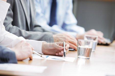 Photo pour Gros plan de mains d'hommes d'affaires lors d'une réunion - image libre de droit