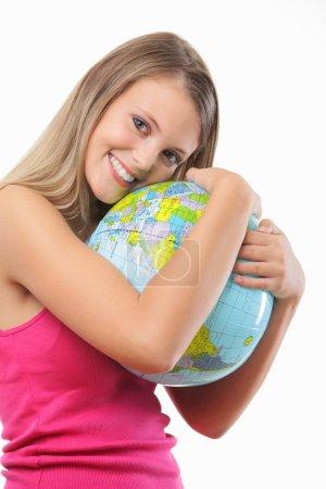Photo pour Portrait d'une fille blonde heureuse embrassant un globe sur fond blanc - image libre de droit