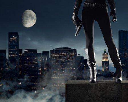 Photo pour Voleur de femme sexy avec pistolet, new york, sur fond - image libre de droit